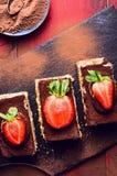 与草莓切片的提拉米苏蛋糕在板岩 免版税库存图片