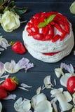 与草莓和花瓣的甜蛋糕在一个木板 免版税图库摄影