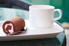 与草莓酱卷蛋糕的咖啡休息。 库存图片