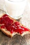 与草莓酱bited垂直的面包 图库摄影