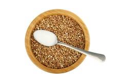 与荞麦和钢匙子的木碗与盐 免版税库存照片