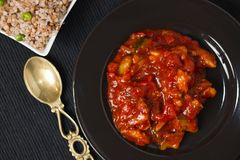 与荞麦配菜的菜炖煮的食物在黑色的盘子和桌布 免版税图库摄影