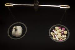 与药片和大蒜的平衡标度 免版税库存图片