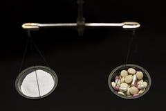 与药片的平衡标度 免版税库存照片