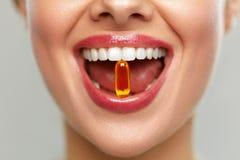 与药片的美丽的妇女嘴在牙 采取维生素的女孩 免版税库存照片