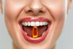 与药片的美丽的妇女嘴在牙 采取维生素的女孩 库存图片