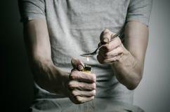 与药物和毒瘾题目的战斗:使拿着匙子打火机上瘾并且加热在一件T恤杉的液体药物在黑暗的ba 库存照片