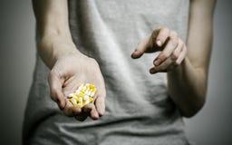 与药物和毒瘾题目的战斗:使拿着在黑暗的背景的麻醉药片上瘾 免版税库存图片