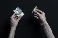 与药物和毒瘾题目的战斗:手上瘾者谎言在一张黑暗的桌上和在它附近是药物,顶面演播室 免版税库存图片