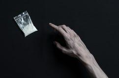 与药物和毒瘾题目的战斗:手上瘾者谎言在一张黑暗的桌上和在它附近是药物,顶面演播室 免版税库存照片
