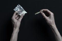 与药物和毒瘾题目的战斗:手上瘾者谎言在一张黑暗的桌上和在它附近是药物,顶面演播室 免版税图库摄影