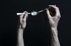 与药物和毒瘾题目的战斗:手上瘾者谎言在一张黑暗的桌上和在它附近是药物,顶面演播室 库存图片