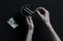 与药物和毒瘾题目的战斗:手上瘾者谎言在一张黑暗的桌上和在它附近是药物,顶面演播室 库存照片