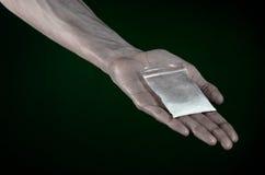 与药物和毒瘾题目的战斗:拿着在深绿背景的肮脏的手袋子上瘾者可卡因在演播室 免版税图库摄影