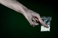 与药物和毒瘾题目的战斗:拿着在深绿背景的肮脏的手袋子上瘾者可卡因在演播室 免版税库存图片