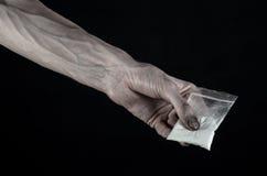 与药物和毒瘾题目的战斗:拿着在黑背景的肮脏的手袋子上瘾者可卡因在演播室 库存照片