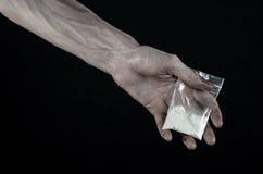 与药物和毒瘾题目的战斗:拿着在黑背景的肮脏的手袋子上瘾者可卡因在演播室 免版税图库摄影