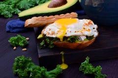 与荷包蛋的三明治用液体卵黄质和无头甘蓝圆白菜 免版税图库摄影