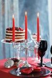 与莓果蛋糕和玻璃的可口甜自助餐用在红色桌上的香槟 免版税库存照片