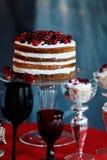 与莓果蛋糕和玻璃的可口甜自助餐用在红色桌上的香槟 库存照片