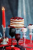 与莓果蛋糕和玻璃的可口甜自助餐用在红色桌上的香槟 免版税库存图片