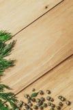 与莳萝和胡椒框架的木背景 免版税图库摄影
