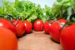 与莴苣叶子的红色爽快蕃茄在木桌背景顶部 家种的菜,健康吃生活方式 免版税库存照片