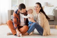 与获得的婴孩的愉快的家庭乐趣在家 库存照片