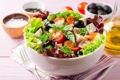 与菜、希腊白软干酪和黑橄榄的新鲜的希腊沙拉在紫色木背景的白色碗 库存照片