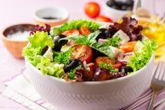 与菜、希腊白软干酪和黑橄榄的新鲜的希腊沙拉在紫色木背景的白色碗 免版税库存图片