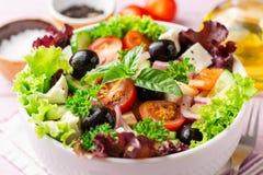 与菜、希腊白软干酪和黑橄榄的新鲜的希腊沙拉在紫色木背景的白色碗 图库摄影