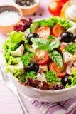 与菜、希腊白软干酪和黑橄榄的新鲜的希腊沙拉在紫色木背景的白色碗 库存图片