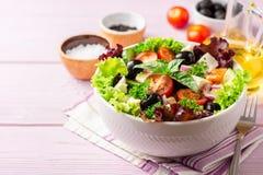 与菜、希腊白软干酪和黑橄榄的新鲜的希腊沙拉在紫色木背景的白色碗 免版税库存照片
