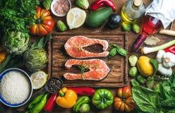 与菜、米、草本、香料和酒的未加工的未煮过的三文鱼鱼在土气木背景的砧板 免版税库存图片