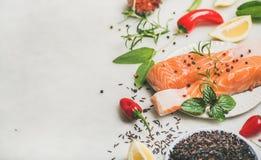 与菜、绿色、米和柠檬的未加工的未煮过的鲑鱼排 库存照片