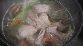与菜、骨头和成份的传统牛肉汤在罐,烹调食谱 在一个烹调罐的汤有杓子的  股票录像