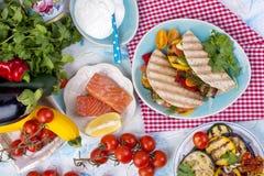 与菜和三文鱼的玉米粉薄烙饼在男性手上 棒谷物节食健身 健康午餐 蔬菜和鱼 夏天菜单 免版税库存照片