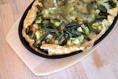 与菜和乳酪的准备的开胃素食薄饼在黑铁卵形平底锅顶视图 免版税图库摄影
