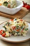 与菜和乳酪的被烘烤的通心面在白色板材服务 免版税图库摄影