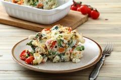 与菜和乳酪的被烘烤的通心面在白色板材服务 免版税库存照片