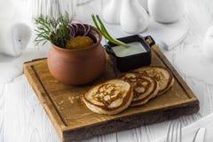 与菜和垂度调味汁的薄煎饼在委员会 免版税库存照片