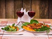 与菜和沙拉的鸡与两杯红葡萄酒 库存照片