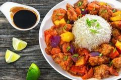 与菜和米的糖醋油煎的猪肉大块 免版税库存图片
