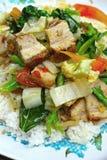 与菜和米的酥脆烤猪肉混乱油炸物。 免版税库存图片