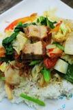与菜和米的酥脆烤猪肉混乱油炸物。 库存照片