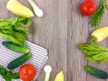 与菜和草本的五颜六色的构成在木背景 平的位置,顶视图 免版税库存图片