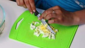 与菜和蛋黄酱的俄国肉沙拉 妇女切在切板的一个煮沸的鸡蛋 股票视频