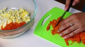 与菜和蛋黄酱的俄国肉沙拉 妇女切在切板的一棵煮沸的红萝卜 股票录像