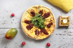 与菜和西红柿酱的比萨与火箭叶子 免版税库存照片