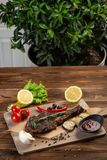 与菜和西红柿酱的羊羔牛排在木背景 免版税图库摄影